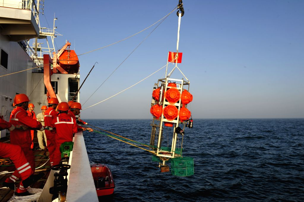 """Staff practice retrieving """"Rainbow Fish,"""" a submersible capable of diving up to 11,000 meters in the sea, on research vessel Zhang Qian in South ..."""
