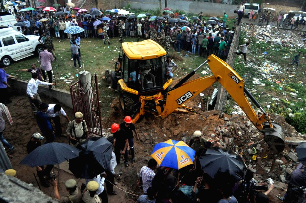 State Disaster Rescue Force (SDRF) personel trying to rescue a two years old baby boy named Akhirul Islam who felt down in a water boring pipe as local prople gather at the spot in Guwahati on May 3,