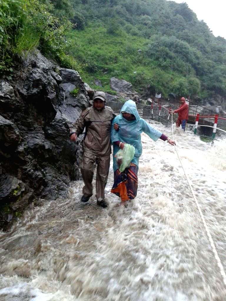State disaster response force (SDRF) personnel rescue pilgrims from Kedarnath after heavy rains washed away roads on June 27, 2015.