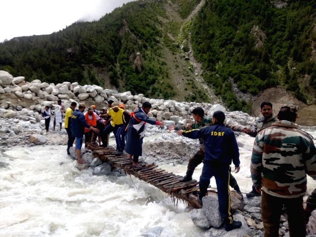 State Disaster Response Fund (SDRF) personnel help Kanwariyas cross the swollen Ganga river through a make shift bridge after a cross bridge collapsed in Uttarakhand's Uttarkashi district ...