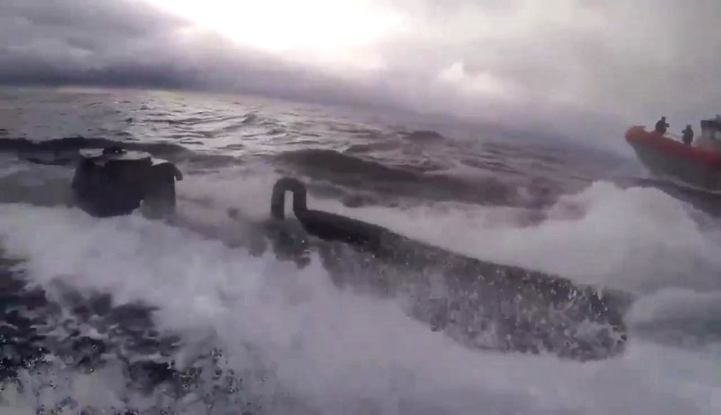 """Stills from a video released by the US Coast Guard where a service member is seen jumping onto a moving semi-submersible vessel -- often called """"narco-submarine"""" -- filled with 16,000 pounds of cocaine worth an estimated $262 million. The crew of the"""