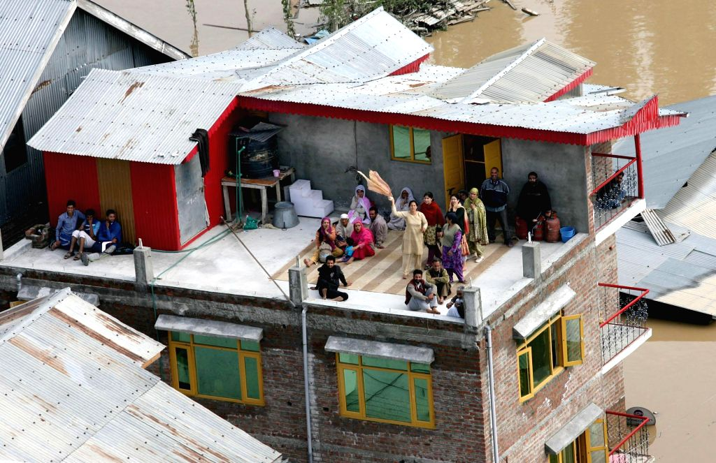 Stranded people signal for help in a flood affected part of Srinagar on September 09, 2014.