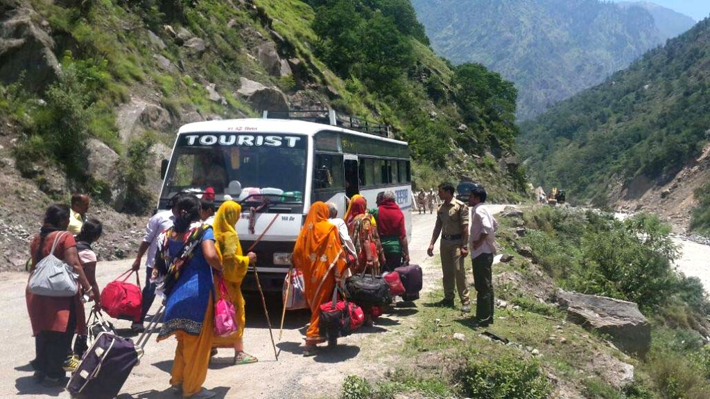 Stranded pilgrims of Hemkunt Saib boarding a bus at Chamoli district after being rescued by State disaster response force (SDRF) personnel in Uttarakhand on June 29, 2015.