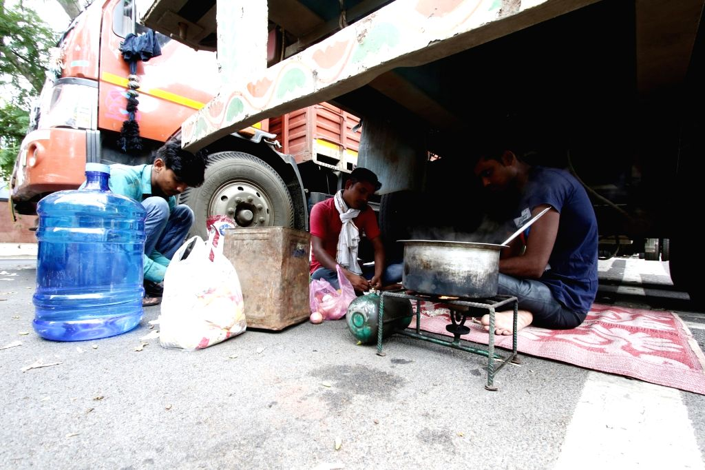 Stranded truckers busy preparing food in the midst of their journey during a complete lockdown imposed in Chennai in the wake of COVID-19 pandemic, on July 1, 2020. Tamil Nadu Chief Minister ... - K. Palaniswami