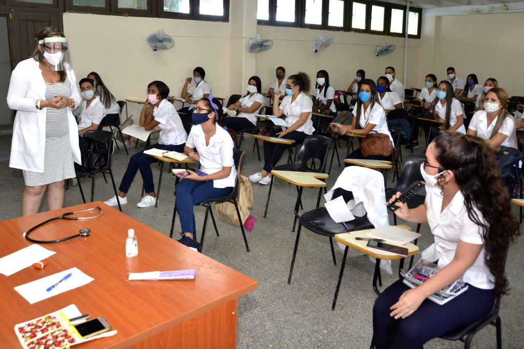 Students and a teacher are seen in a classroom of a medical college in Cienfuegos Province of Cuba, Sept. 1, 2020. Schools in most parts of Cuba reopened on ...