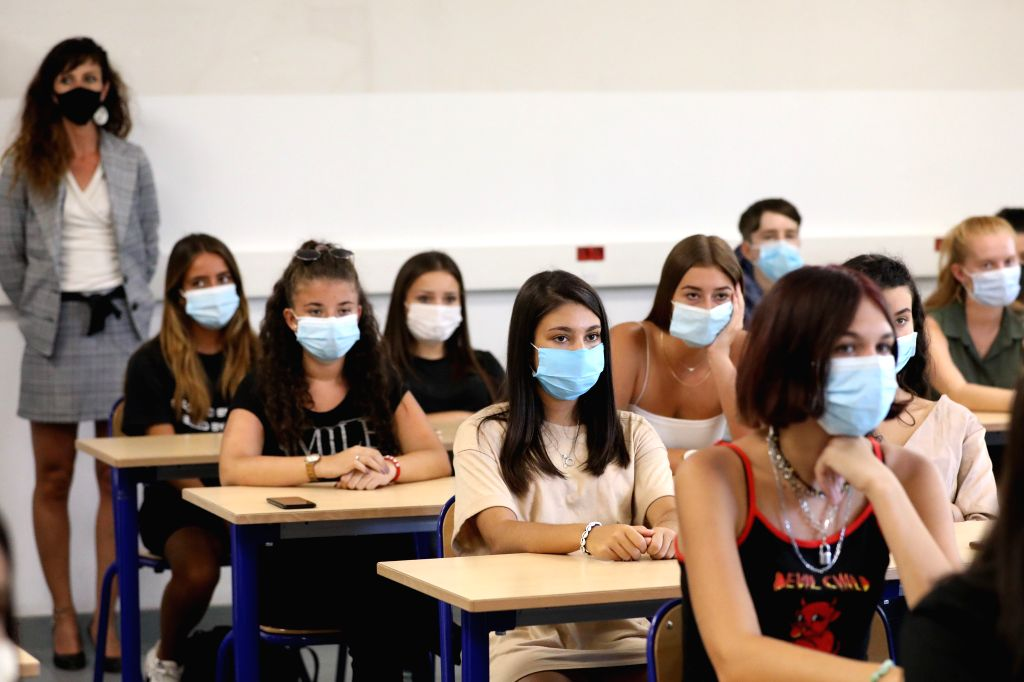 Students and a teacher wearing protective masks attend a class at a high school on the first day of the new school year in Nice, southern France, Sept. 1, 2020. The ...