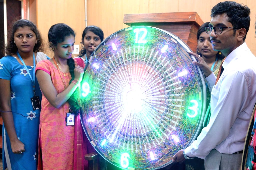 Students and faculty of the Sapthagiri College of Engineering show a digital clock based on GPS signals developed by them that displays time like traditional clocks, at a press conference ...