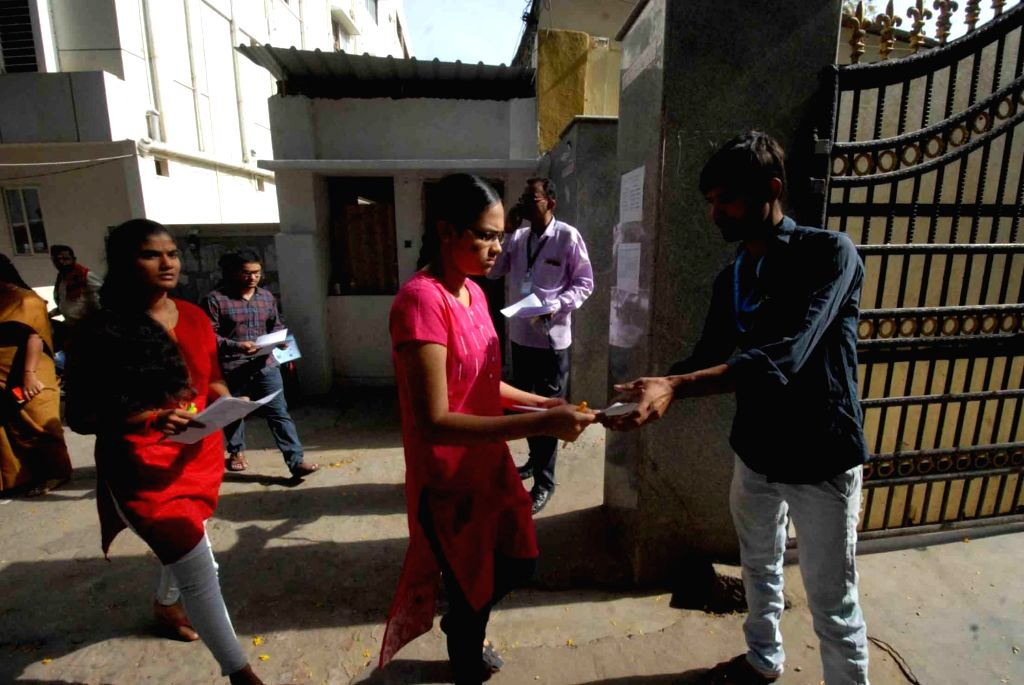 Students appearing for the 2019 Engineering, Agriculture and Medical Common Entrance Test (EAMCET), get their admit cards checked before getting entry to their examination center, in ...