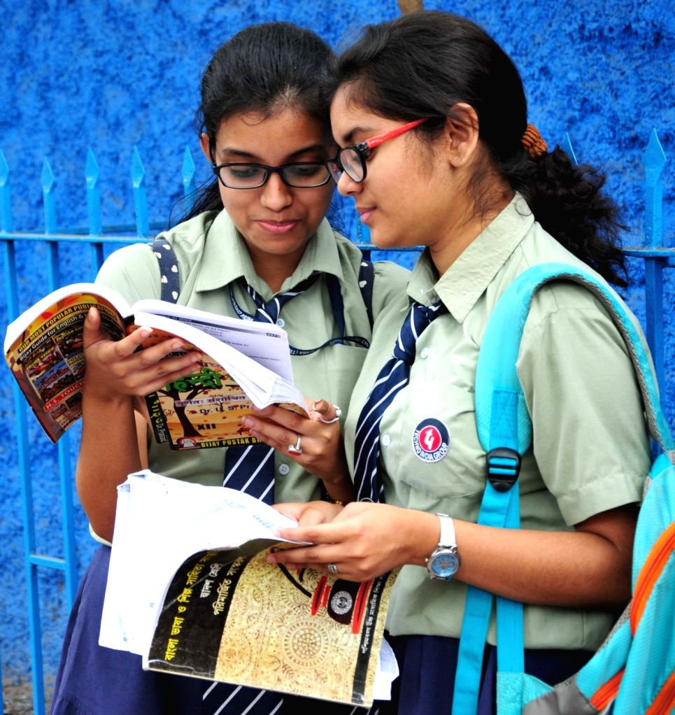Students appearing for their class 12th Board examinations, busy in last-minute revision outside their exam center in Kolkata on March 27, 2018.