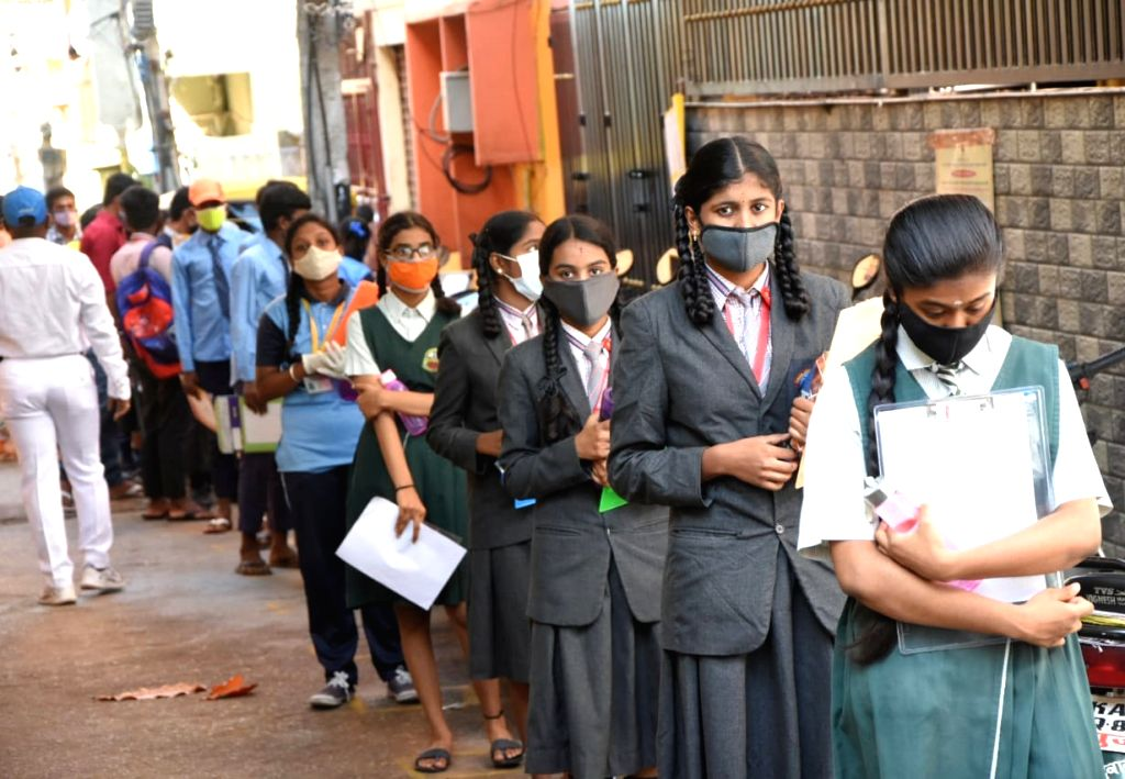 Students arriving to appear for their remaining Secondary School Leaving Certificate (SSLC) examinations queue up to undergo thermal screening for COVID-19, in Bengaluru on June 25, 2020.