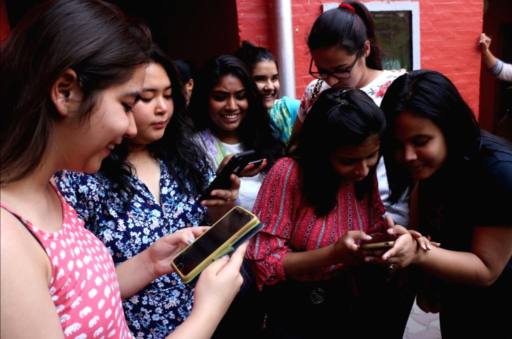 Students check their results after the Central Board of Secondary Education (CBSE) declared results of the class 12 examinations, in New Delhi on May 26, 2018.