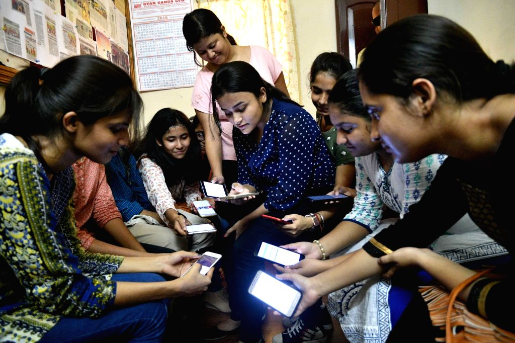 Students check their results on their smartphones after the Central Board of Secondary Education (CBSE) declared results of the class 12 examinations, in Patna on May 26, 2018.