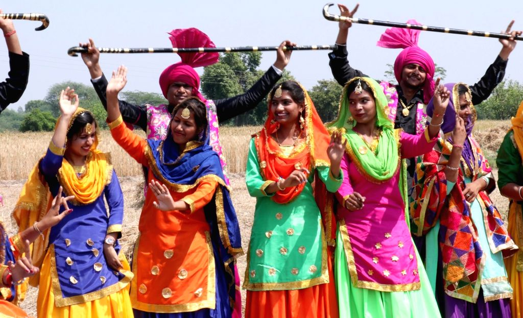 Students dressed up in traditional attires participate in rehearsals at a wheat field ahead of Baisakhi celebrations in Punjab's Mohali, on April 9, 2019.