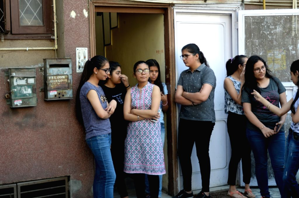 Students gather outside the coaching centre, the owner of which is being questioned by the Delhi Police in connection with the leak of question papers of Class 10 and 12, based on a ...