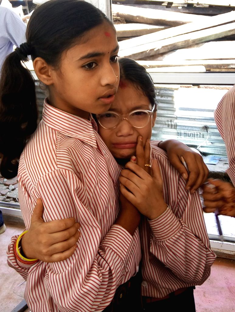 Students hold each other at a school after an aftershock of 4.3 magnitude struck with an epicenter in the capital in Kathmandu, Nepal, Aug. 11, 2015. Nepalese ...