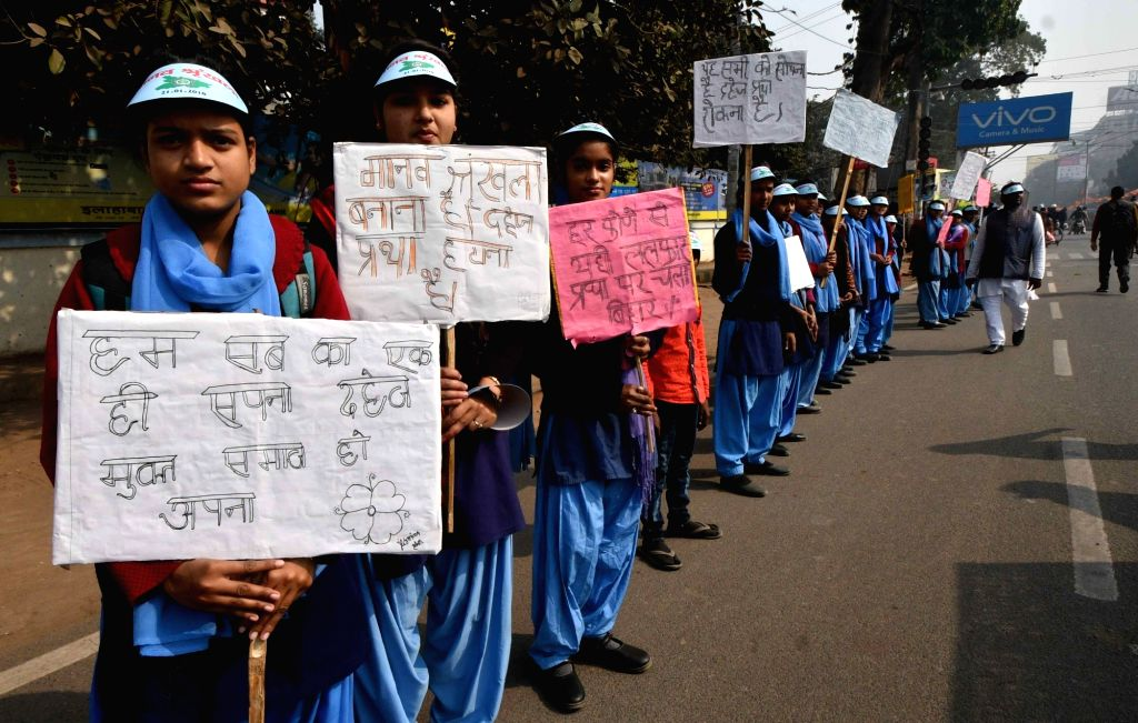Students hold placards with various social messages on dowry and child marriage during human chain formation in Patna on Jan 21, 2018.