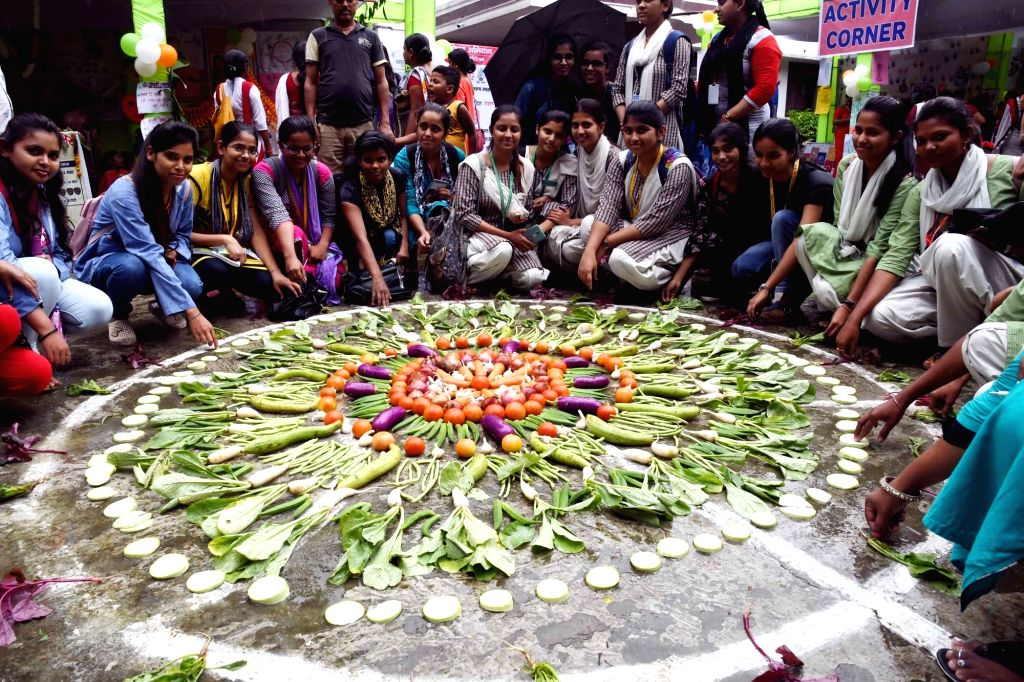 """Students of Magadh Mahila College form rangoli from vegetables during """"Poshan Mela"""" in Patna, on Sep 27, 2019."""