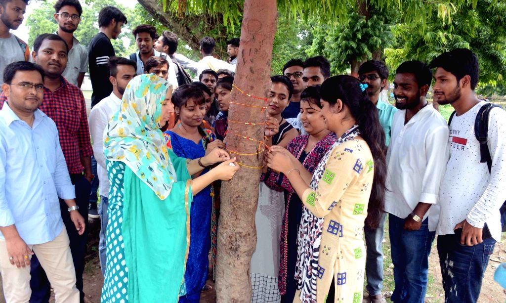 Students of Patna University tie 'rakhis' to a tree in a bid to create awareness among people, in Patna on Aug 10, 2019.
