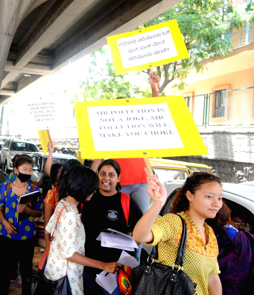 Students of St. Joseph College hold placards and shout slogans to create awareness for saving fuel, against tree cutting and curb pollution at Double Road, in Bangalore on June 16, 2014.