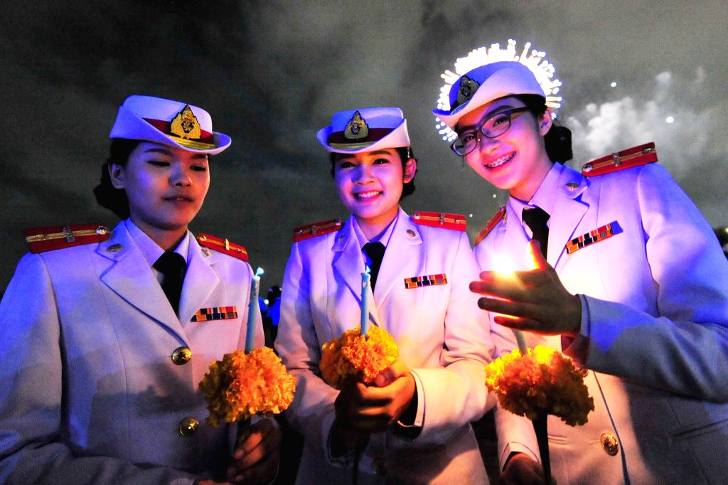 Students of the Royal Thai Army Nursing holds candles to celebrate Queen Sirikit's 83rd birthday at the Sanam Luang square in Bangkok, Thailand, Aug. 12, 2015. ...