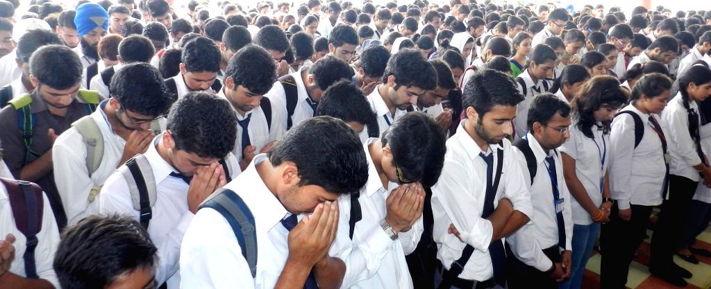 Students pray for the well being of the victims of Jammu and Kashmir floods in Mohali, Punjab on Sept 10, 2014.
