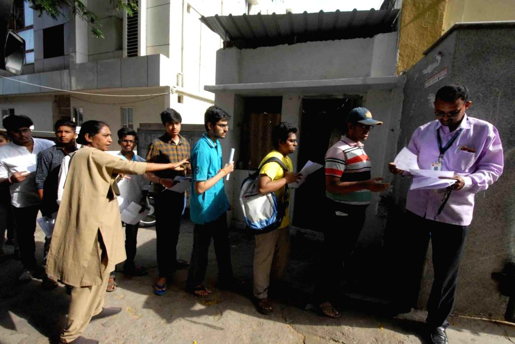 Students queue up outside an examination center to appear for the 2019 Engineering, Agriculture and Medical Common Entrance Test (EAMCET) that commenced in Telangana and Andhra Pradesh; in ...