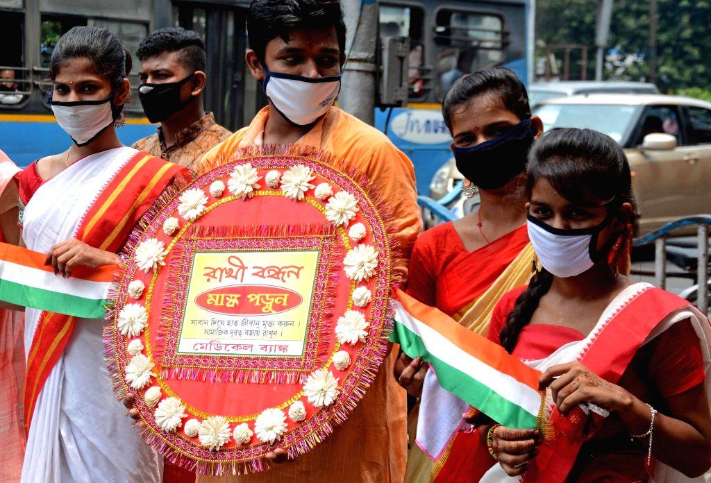 Students raise awareness about maintaining social distancing, wearing masks and using sanitisers amid COVID-19 pandemic, during Raksha Bandhan celebrations, in Kolkata on Aug 3, 2020.