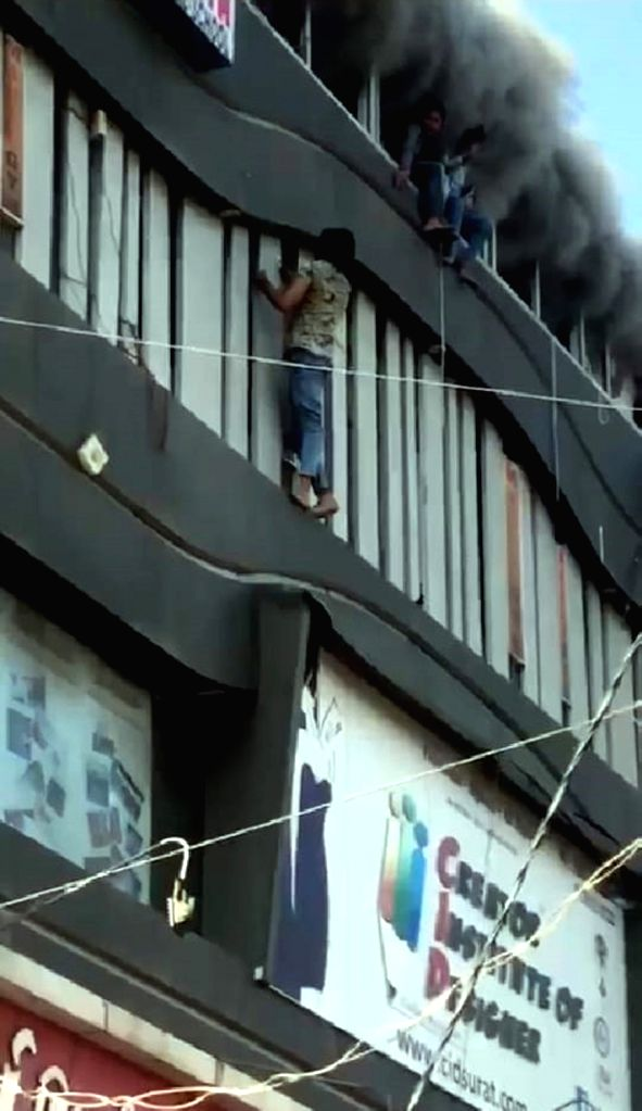 Students try to escape the massive fire that broke out at a coaching centre atop a four-storey building, by jumping off the building in panic, in Sarthana area of Gujarat's Surat on May 24, ...