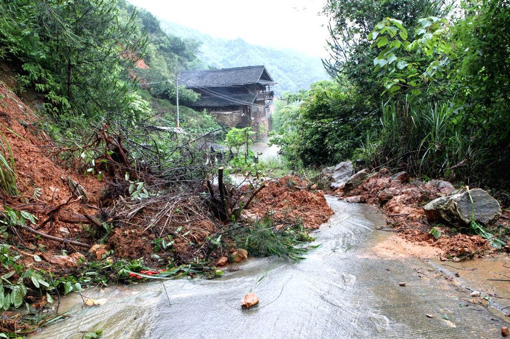 SUINING, June 26, 2017 - A road is blocked by stones and mud due to heavy rain in Zhiping village in Suining county of Shaoyang City, central China's Hunan Province, June 26, 2017. China issued a ...