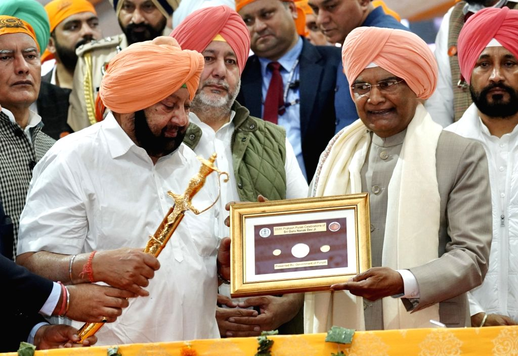 Sultanpur Lodhi: President Ram Nath Kovind being presented with a memento by Punjab Chief Minister Captain Amarinder Singh during the 55oth birth anniversary celebrations of Guru Nanak Dev in ... - Captain Amarinder Singh, Nath Kovind and Nanak Dev