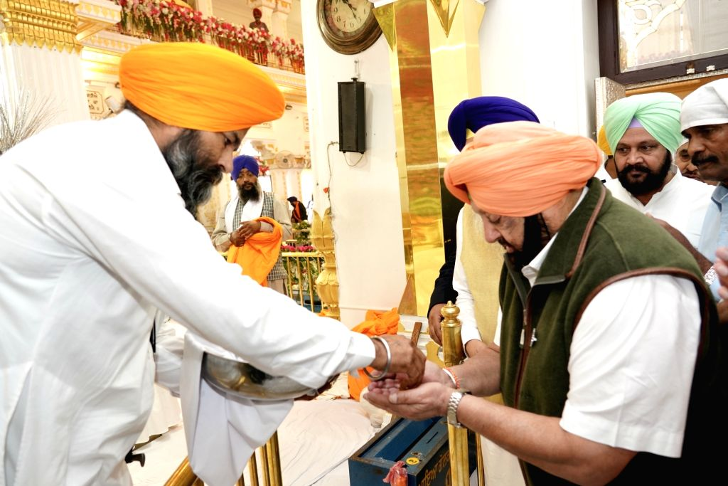 Sultanpur Lodhi: Punjab Chief Minister Captain Amarinder Singh being offered deg (karah Prasad) during the 550th birth anniversary celebrations of Guru Nanak Dev in Sultanpur Lodhi, Punjab on Nov 12, ... - Captain Amarinder Singh and Nanak Dev