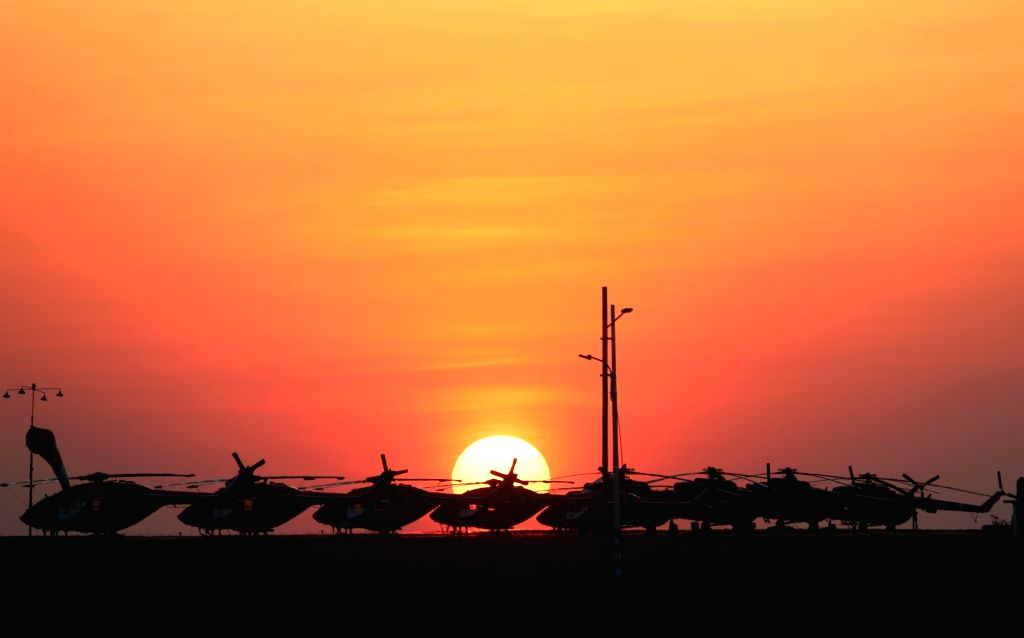 Sun is setting against the backdrop parked Sarang helicopters during the last day of the 12th edition of AERO India 2019 at Yelahanka Airbase, in Bengaluru on Feb 24, 2019.