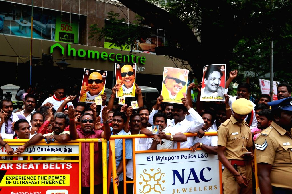 Supporters holding portraits of  DMK President M. Karunanidhi wait outside the Kauvery Hospital where he is admitted, in Chennai, on Aug 7, 2018.