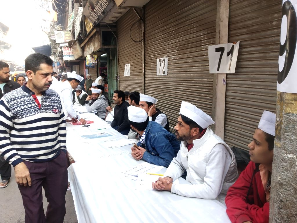 Supporters of Delhi Cabinet Minister and AAP's candidate from Ballimaran assembly seat, Imran Hussain seen volunteering in white jackets and caps, during voting for Delhi Assembly ...