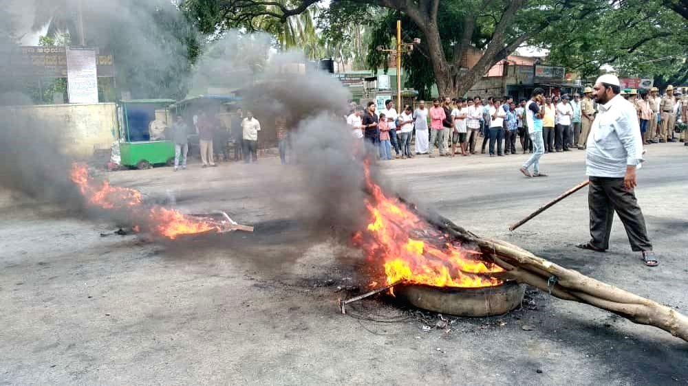 Supporters of Karnataka Congress leader D.K. Shivakumar burn a tyre after he was arrested on Tuesday evening by the Enforcement Directorate following four days of questioning in connection ...