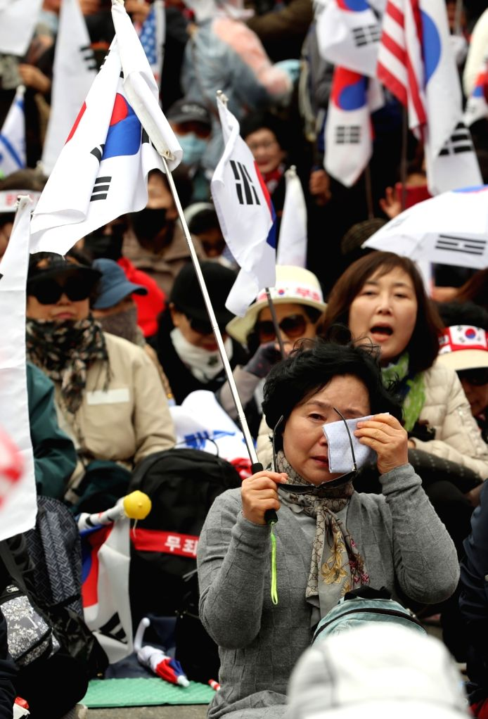 Supporters of ousted former President Park Geun-hye shed tears in front of the Seoul Central District Court on hearing the news that she was sentenced to 24 years in jail and fined 18 billion ...