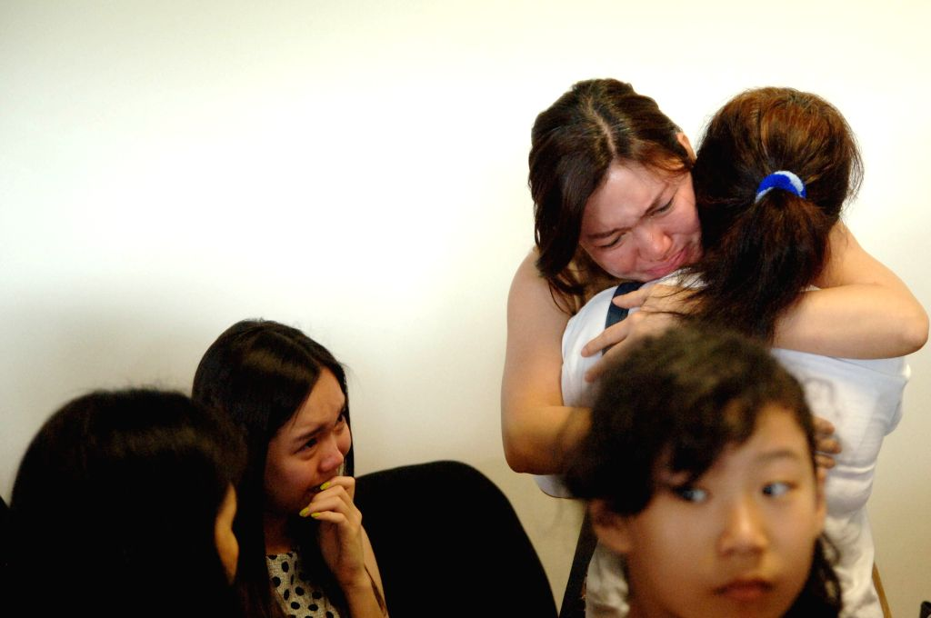 Relatives of the passengers on AirAsia missing flight QZ8501 cry at Juanda international airport in Surabaya of East Java, Indonesia, Dec. 28, 2014. The flight ...