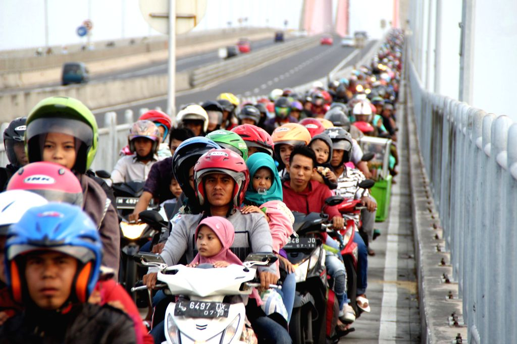 SURABAYA, June 13, 2018 - Thousands of Indonesians ride motorcycles to home on the Suramadu bridge in Surabaya, East Java, Indonesia, June 13, 2018. Indonesia's traffic reached its peak each year ...
