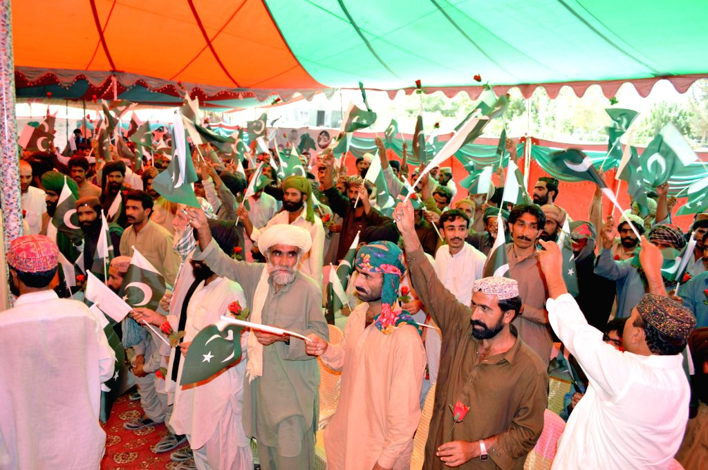 Surrendered militants wave national flags during a ceremony in southwest Pakistan's Quetta, Aug. 14, 2015. About 400 militants surrendered in a ceremony held on the ...