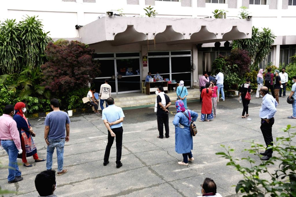 Suspected COVID-19 patients wait to give their samples for coronavirus testing at Patliputra Ashok Hotel isolation centre while maintaining social distancing, in Patna during a re-imposed ...