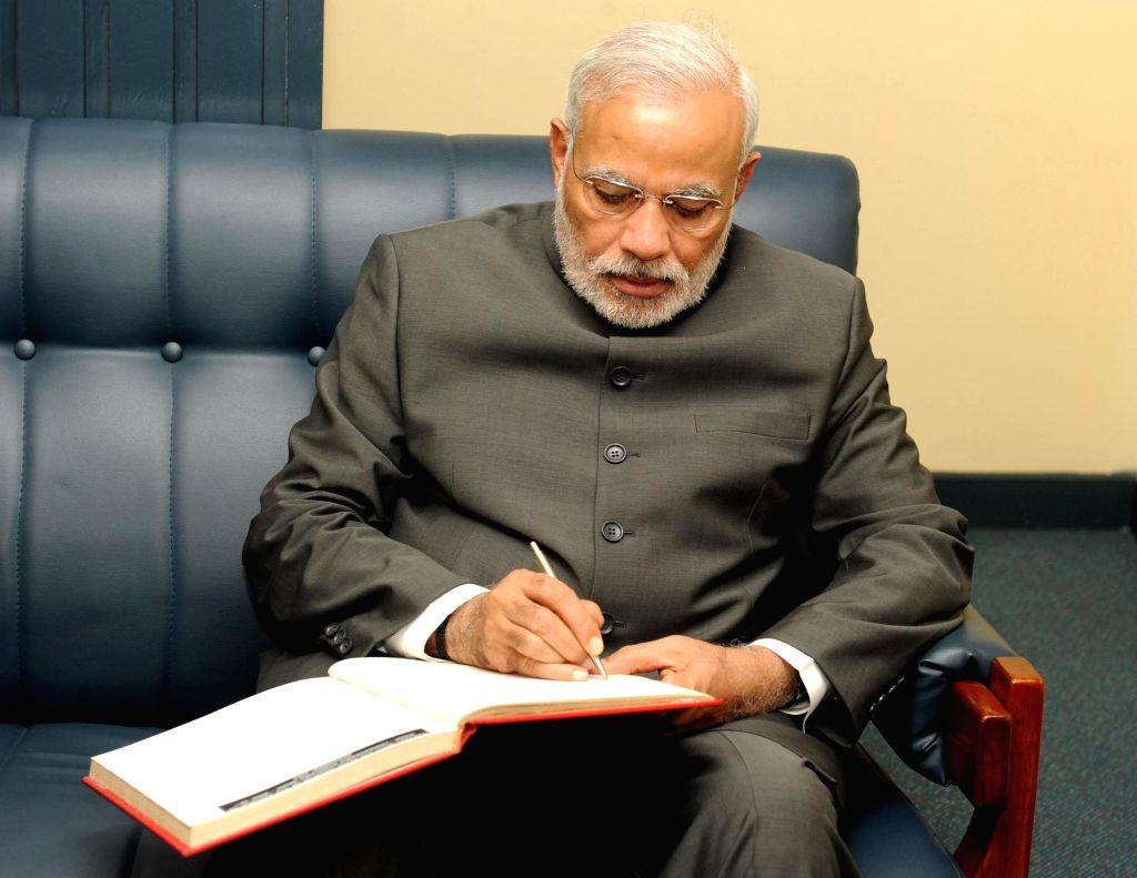 Prime Minister, Narendra Modi signs the visitors' book at the PMO, in Suva, Fiji on Nov 19, 2014. - Narendra Modi