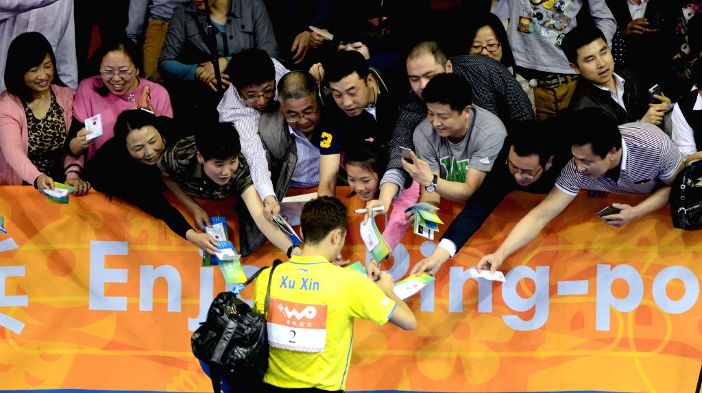 China's Xu Xin(Bottom) autographs for the audience after winning the Mixed Doubles match against Germany's Steffen Mengel/Petrissa Solja at the 53rd Table Tennis ...