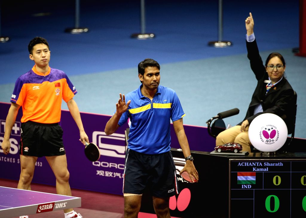 India's Sharath Kamal Achanta(C) quits after his first shot during his Men's Singles match against China's Fang Bo at the 53rd Table Tennis World Championships in ...