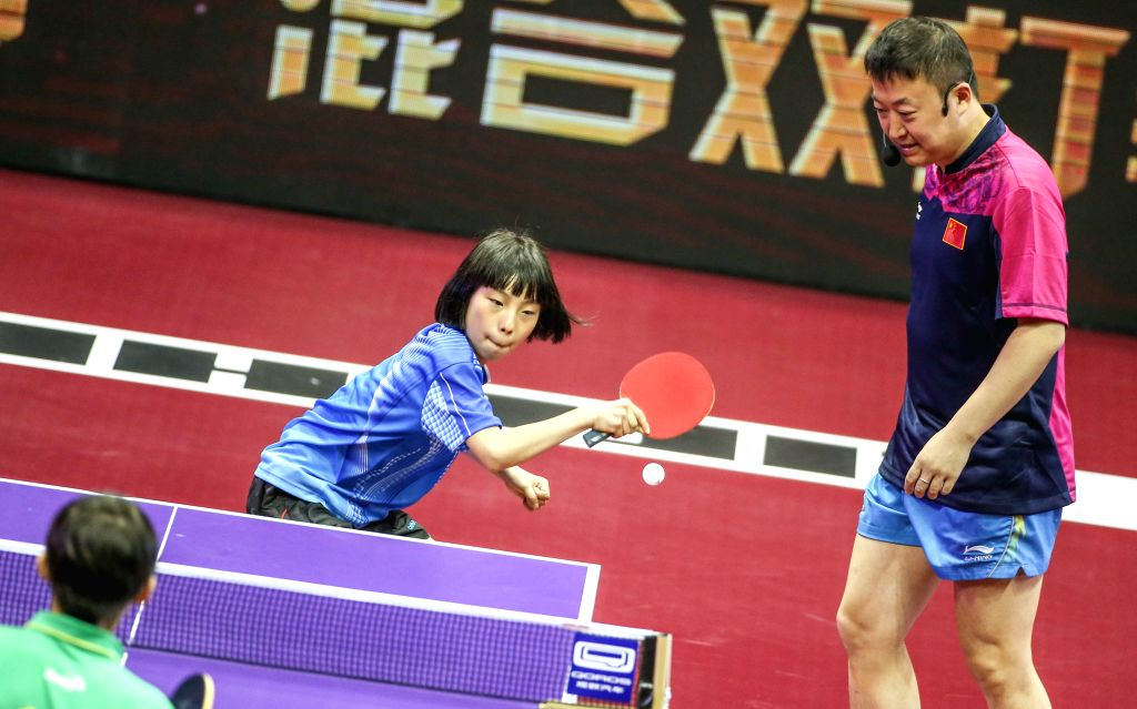 Famous Chinese table tennis player Ma Lin(R) interacts with fans during a promotional match at the 53rd Table Tennis World Championships in Suzhou, city of east ...