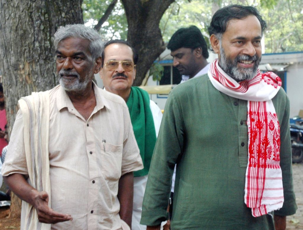 Swaraj India president Yogendra Yadav and member of the national committee of the party Devanur Mahadeva arrive to attend a panel discussion, in Bengaluru on April 3, 2018. - Yogendra Yadav