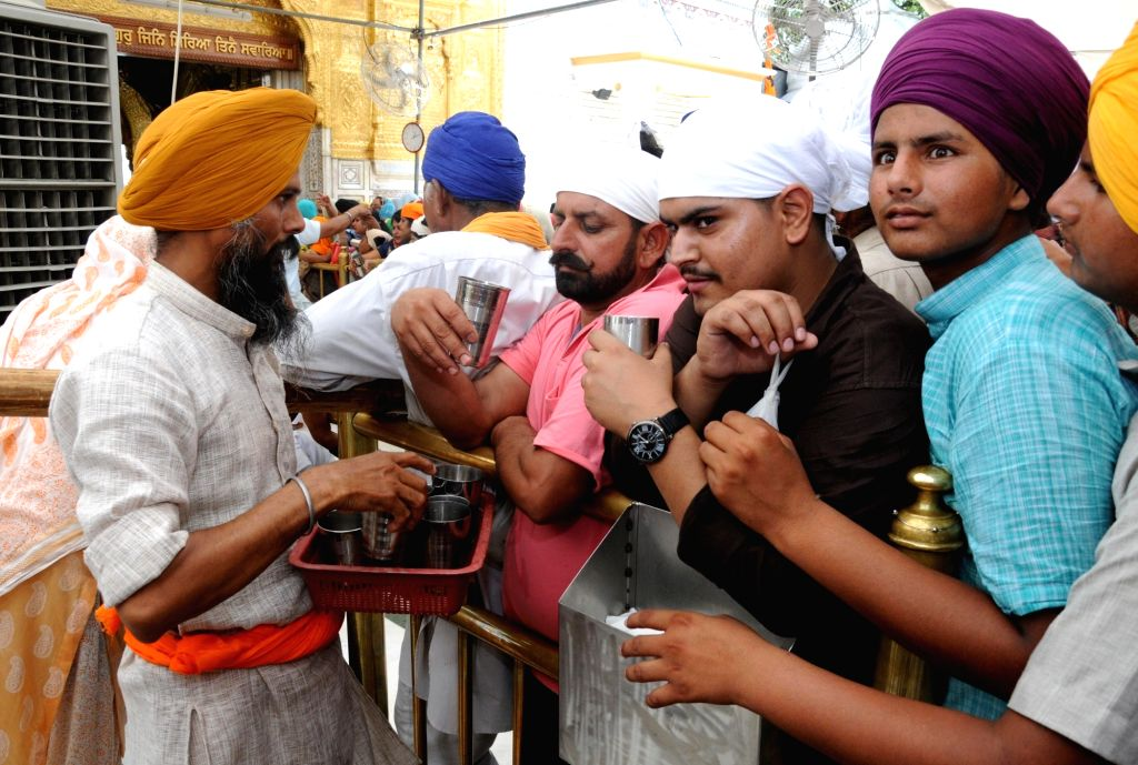 Sweetened water being distributed among devotees on a hot sunny day at Golden Temple in Amritsar, on June 3, 2019.