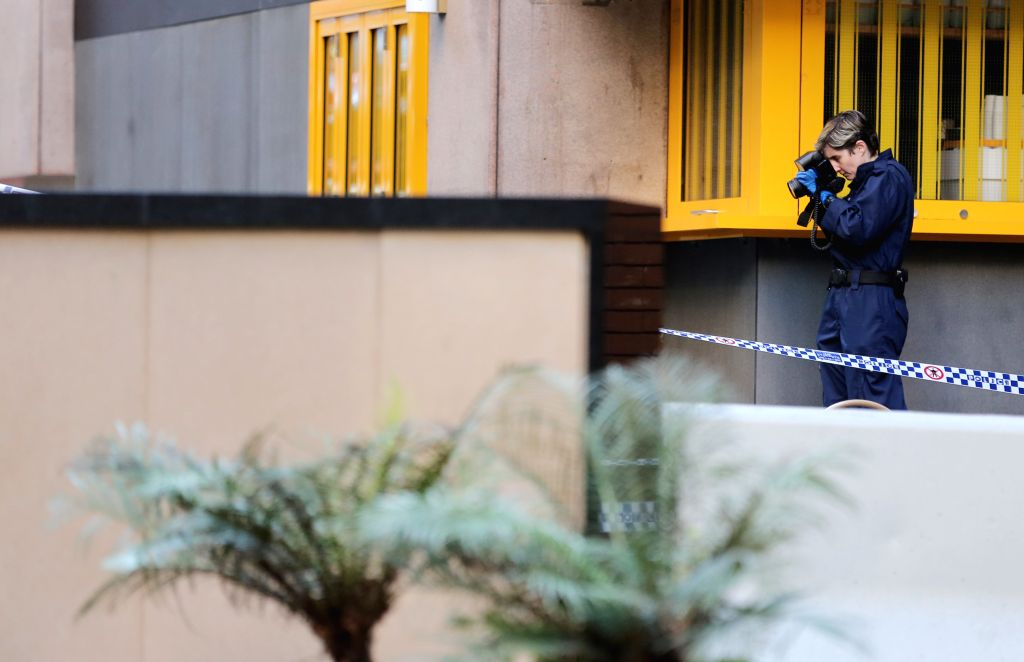 SYDNEY, Aug. 13, 2019 - A police officer takes photos at the site of the knife attack in Sydney, Australia, Aug. 13, 2019. A woman was killed and at least two others were injured after a man ...