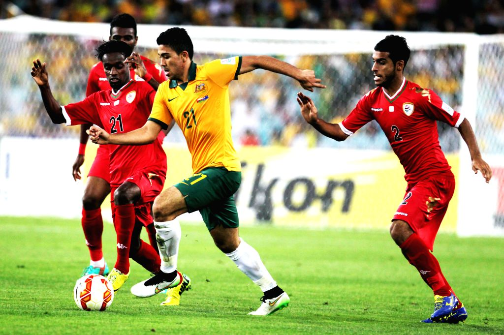 Massimo Luongo (2nd R) of Australia vies with Mohsin Al Khaldi (L front) of Oman during a Group A match at the AFC Asian Cup in Sydney, Australia, Jan. 13, 2015. ...