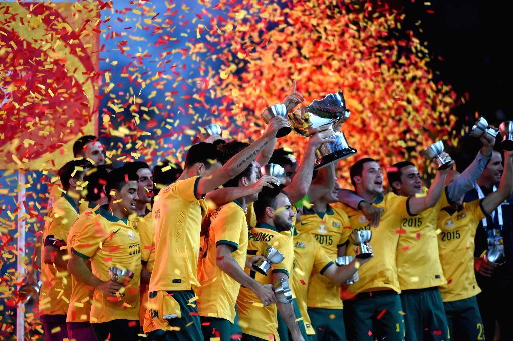 Australian players celebrate with the Asian Cup trophy after winning the final match against South Korea at the 2015 AFC Asian Cup in Sydney, Australia, Jan. 31, ...