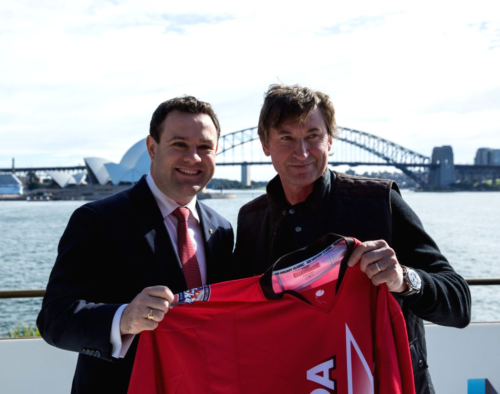 SYDNEY, June 23, 2016 - Ice Hockey player Wayne Gretzky (R) and New South Wales Minister for Trade, Tourism and Major Events Stuart Ayres pose for a photo holding a jersey in Sydney, Australia, June ...